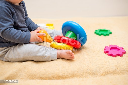 istock Cute baby playing with colorful toy pyramid in light bedroom. Toys for little kids. Child with educational toy. Early development. 1150698014