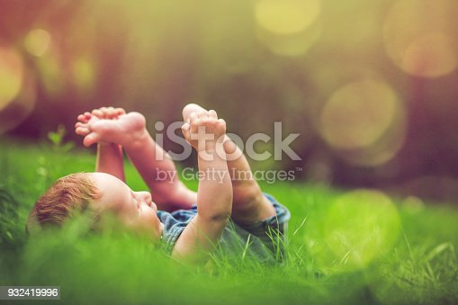 Happy baby boy laying on the grass in summer