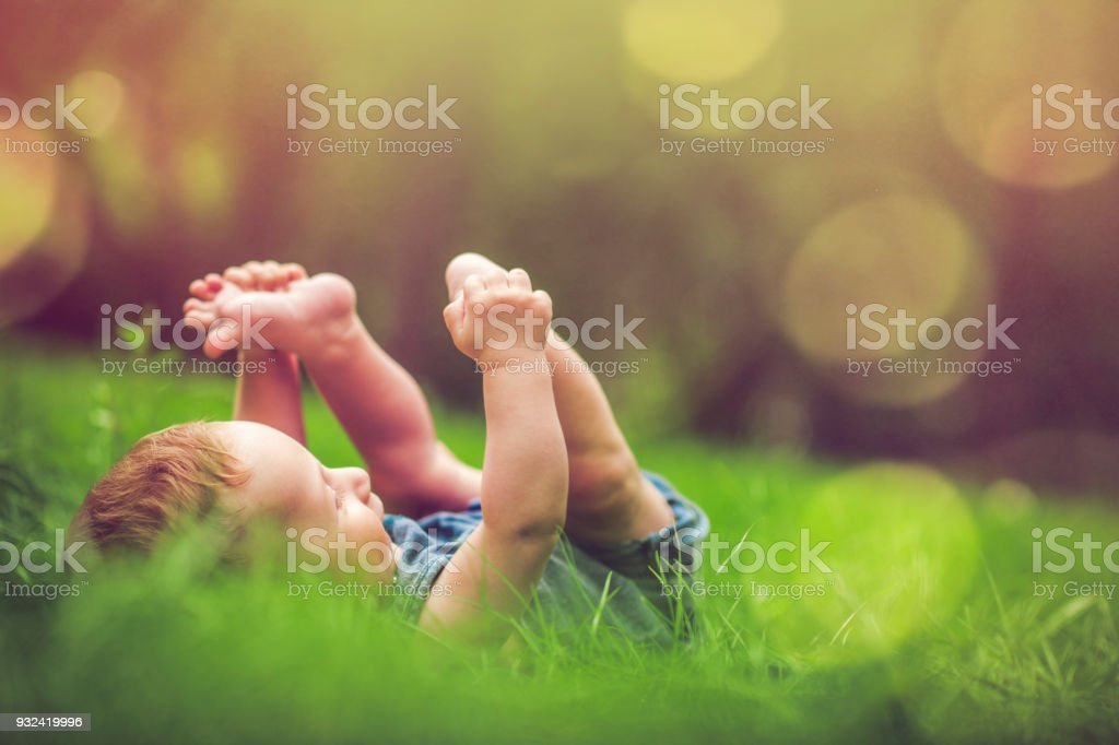 Cute baby playing with his legs on the grass stock photo