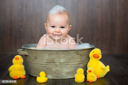 istock Cute baby playing with rubber duck while sitting in metal basin 923848446