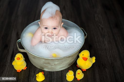 istock Cute baby playing with rubber duck while sitting in metal basin 923848524