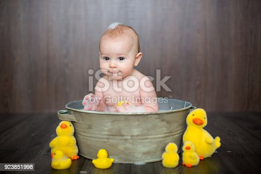 istock Cute baby playing with rubber duck while sitting in metal basin 923851998