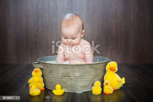 istock Cute baby playing with rubber duck while sitting in metal basin 923852112