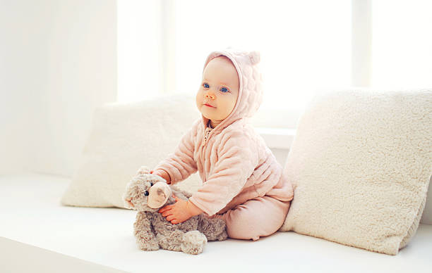 Cute baby playing with teddy bear toy home stock photo