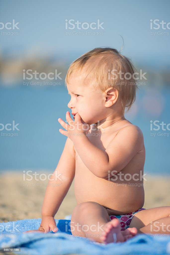 Cute baby playing with toys on sandy beach near the stock photo