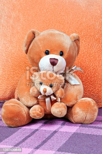 Cute baby plush toys - a bear holds in the paws of a little teddy bear