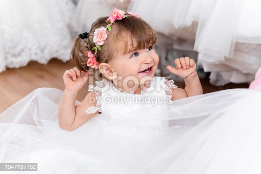 Portrait of 18 months old baby girl smiling and playing at store. Small girl wearing flower wreath and trying on dress at bridal boutique.
