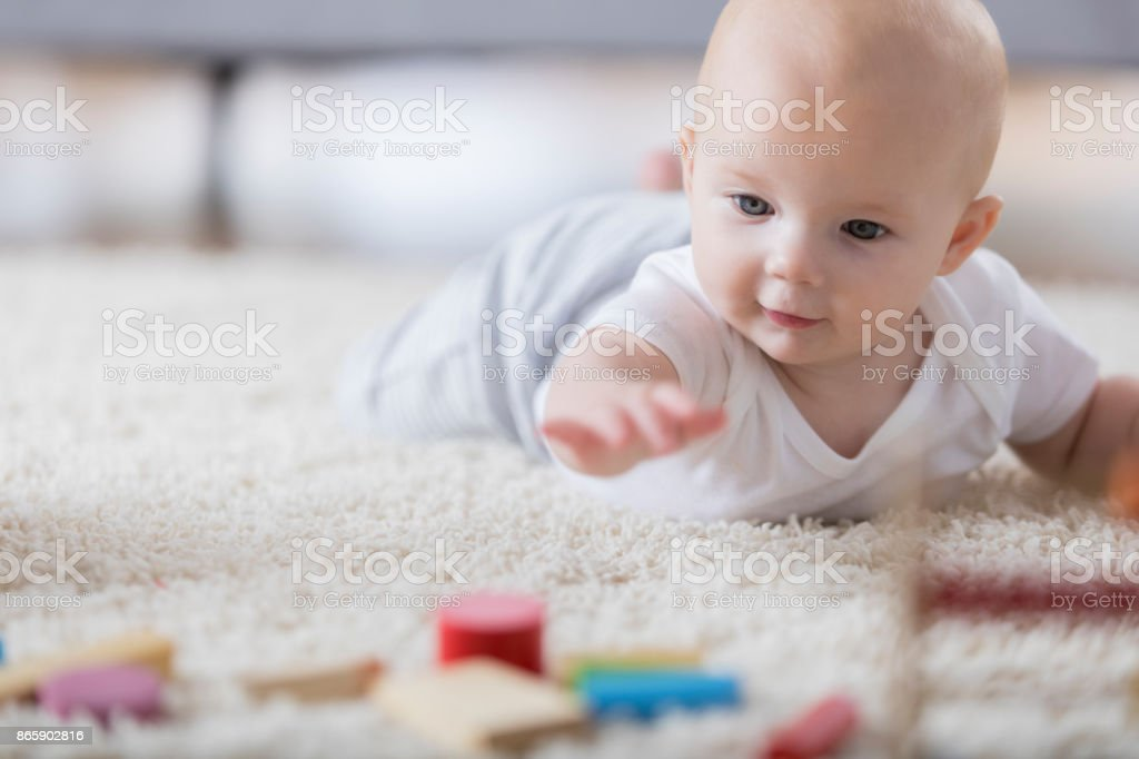 Cute baby reaches for wooden toys on living room rug stock photo