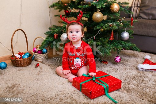 istock Cute baby reindeer holding Christmas gifts at christmas tree at home room 1069124260