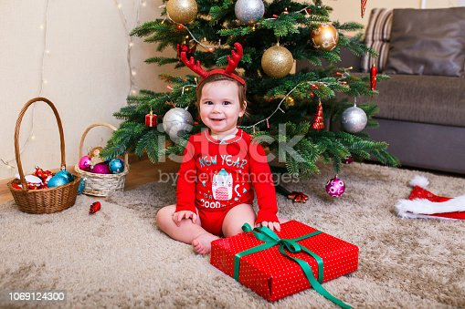 istock Cute baby reindeer holding Christmas gifts at christmas tree at home room 1069124300