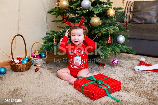 istock Cute baby reindeer holding Christmas gifts at christmas tree at home room 1069124356