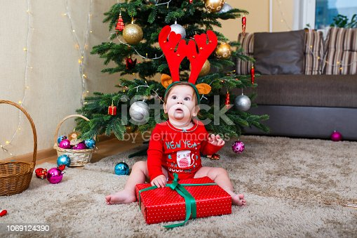 istock Cute baby reindeer holding Christmas gifts at christmas tree at home room 1069124390