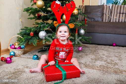 istock Cute baby reindeer holding Christmas gifts at christmas tree at home room 1069124520