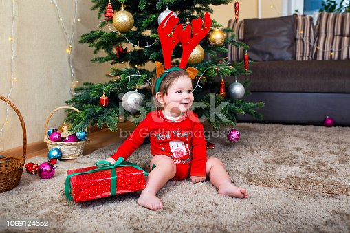 istock Cute baby reindeer holding Christmas gifts at christmas tree at home room 1069124552