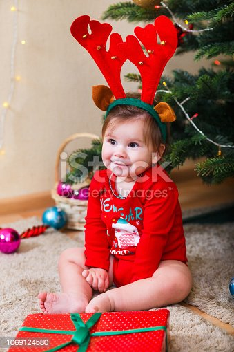 istock Cute baby reindeer holding Christmas gifts at christmas tree at home room 1069124580