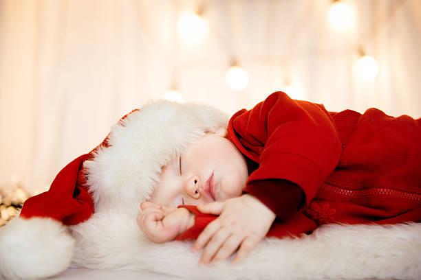 Cute baby santa sleeping stock photo