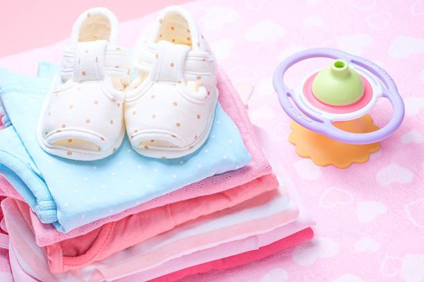 Linda zapatos de bebé para niños en pila de ropa de bebés. - foto de stock