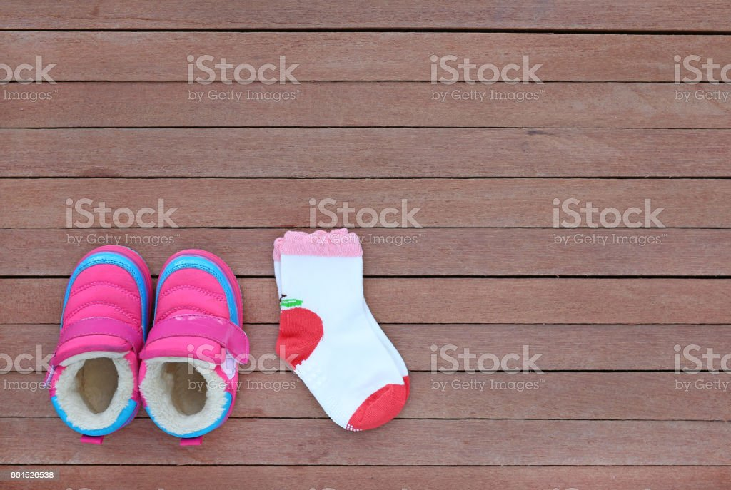 Cute baby shoes with socks on wood plank. royalty-free stock photo
