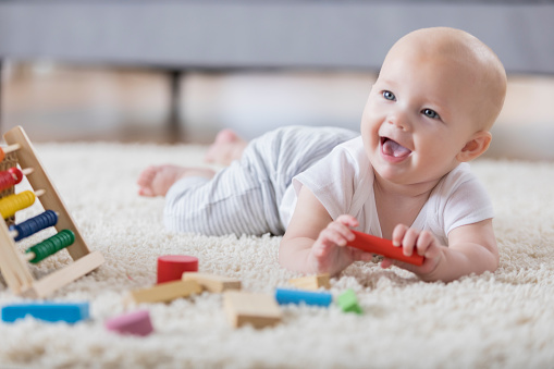 A cute baby lays on her tummy on a rug in a living room and sings with an open mouthed smile.  She is holding one of several wooden blocks.  There is an abacus in the foreground.