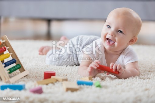 istock Cute baby sings with open mouth while playing with wooden blocks 865900638