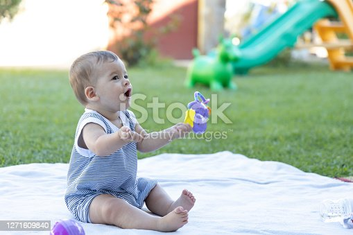 Cute baby sitting and laughing in the garden at home.