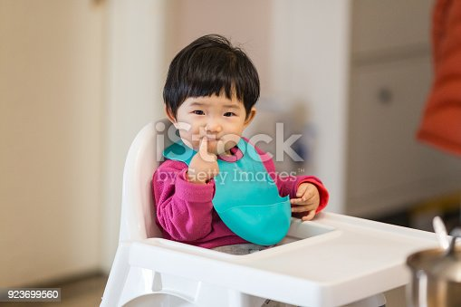 istock Cute baby Sitting in a high chair waiting for to eat dinner 923699560