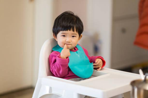 niedliche baby sitzen in einen hochstuhl zu abend essen warten - kinderstuhl und tisch stock-fotos und bilder