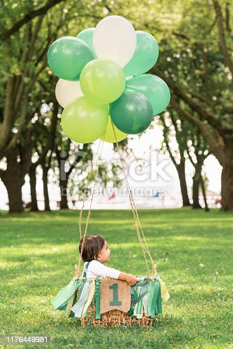 istock Cute baby sitting in a wowen basket with balloons and a green ribbon banner that reads