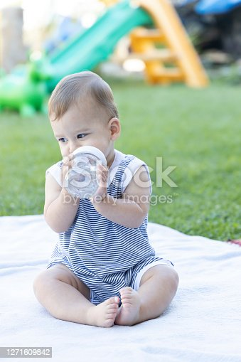 Cute Baby sitting in the yard at home drinking