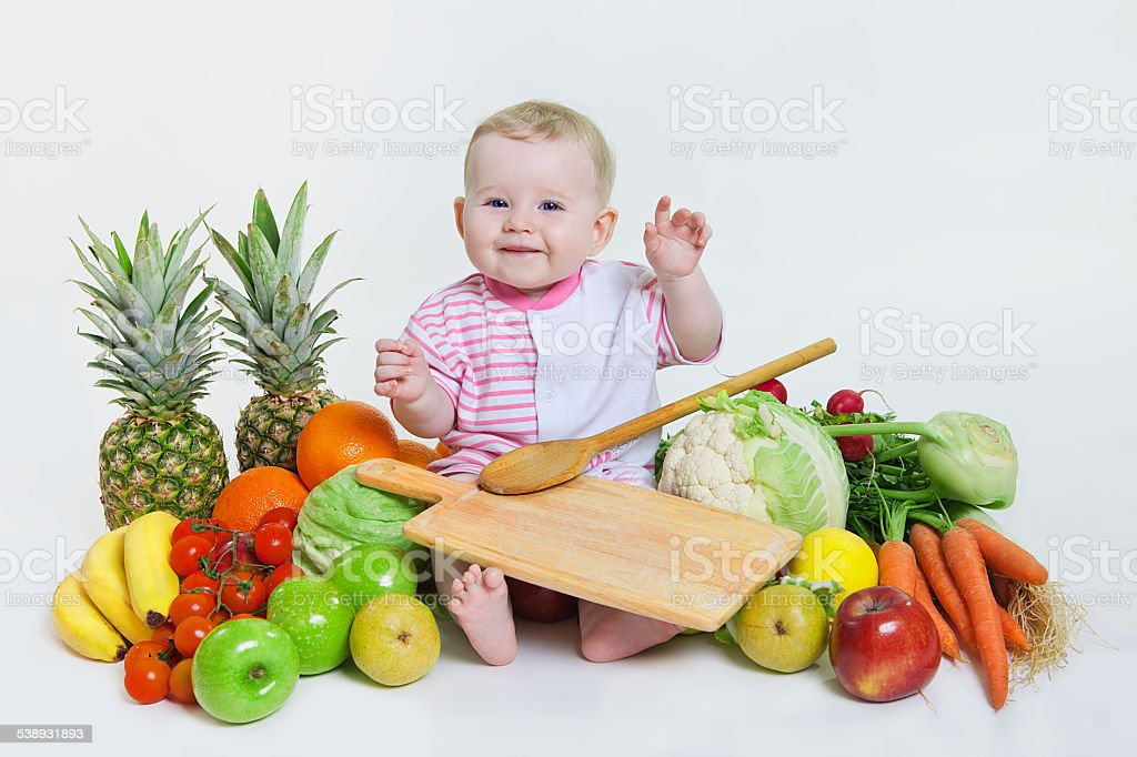 Cute baby sitting with fruits and vegetables stock photo