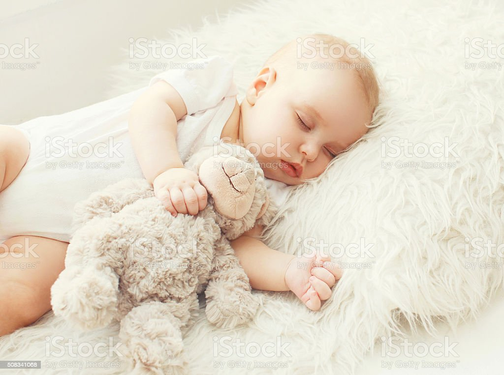 Cute baby sleeping on soft bed at home stock photo