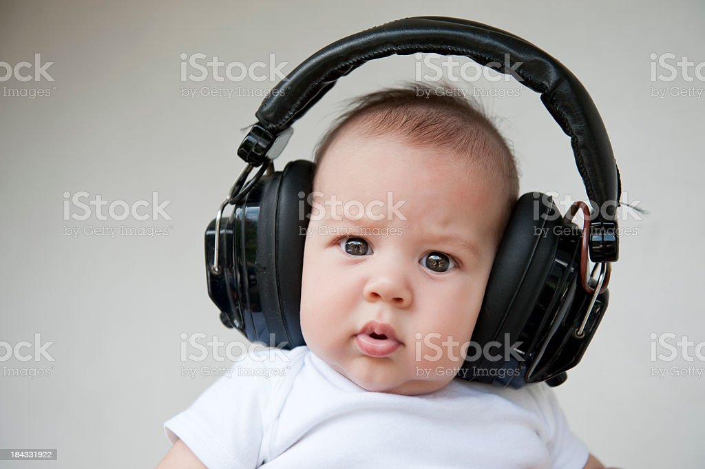 A cute baby wearing big headphones royalty-free stock photo