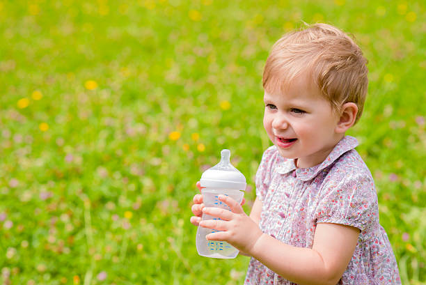Cute baby with a bottle in nature stock photo