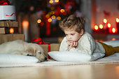 Cute baby with a white golden labrador on the background of Christmas decorations.