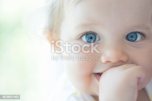 Cute baby with big blue eyes, holding her finger in her mouth, extreme close up.