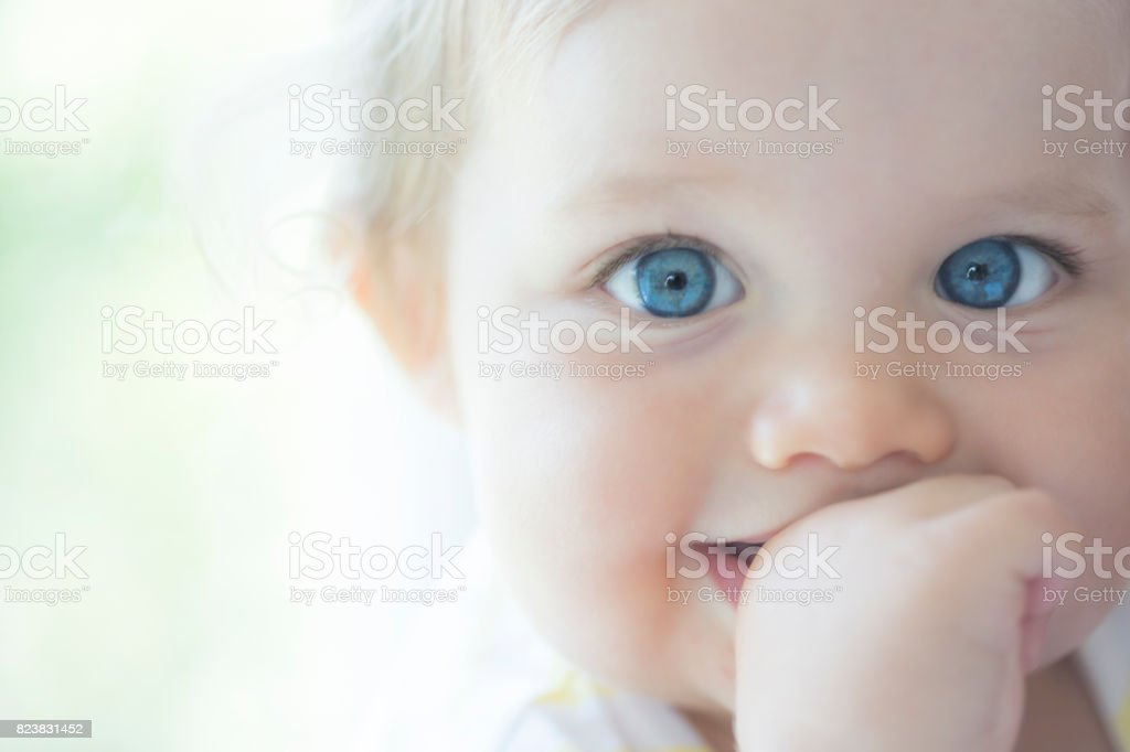 Cute baby with big blue eyes stock photo