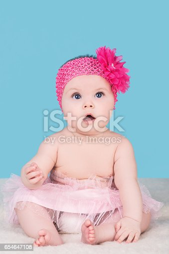 istock cute baby with pink bow flower on head 654647108