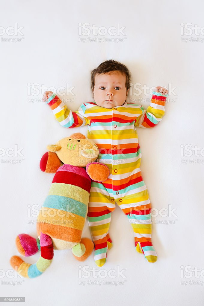 Cute baby with Striped colored pajamas and a  cat toy stock photo