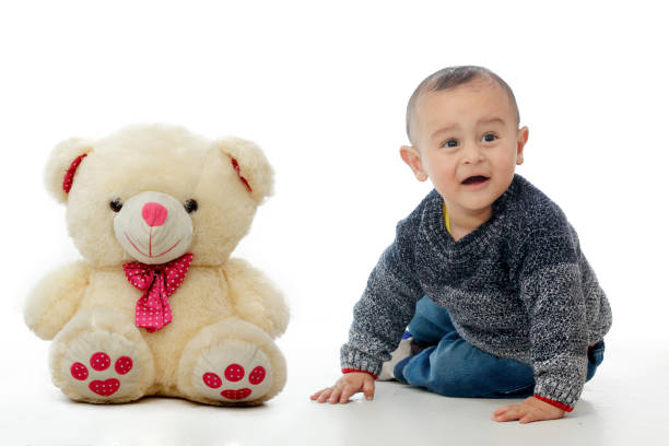 Cute baby with Teddy bear Cute baby with Teddy bear looking away teddy bear stock pictures, royalty-free photos & images