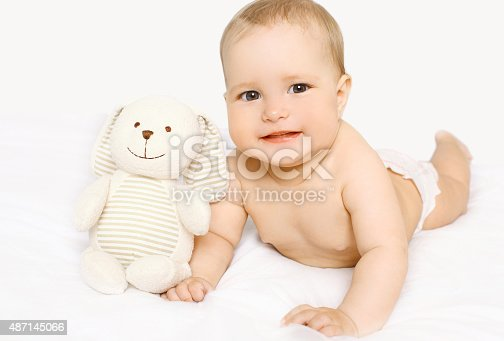 1084486306 istock photo Cute baby with toy lying on the bed at home 487145066