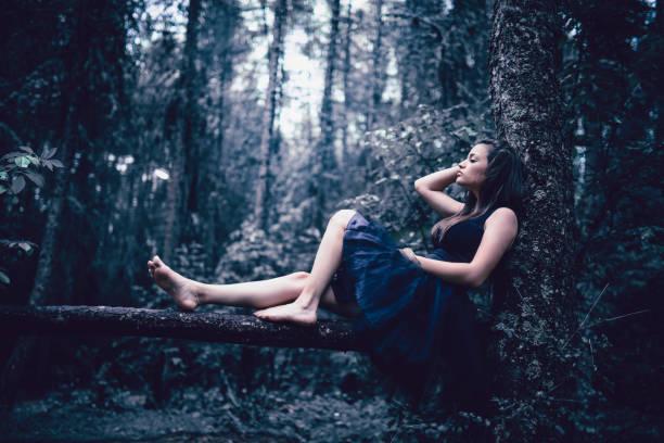 süße barfuß frau sitzend auf ast im regenwald - gothic kleid stock-fotos und bilder