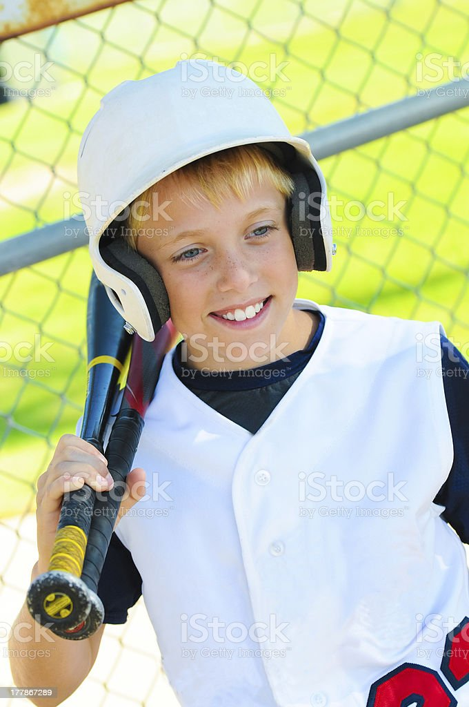 Cute baseball player in dugout royalty-free stock photo