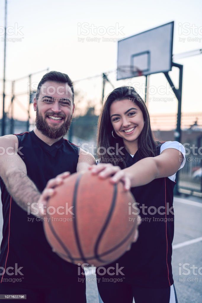 Cute Basketball Couple Posing With a Ball After Training