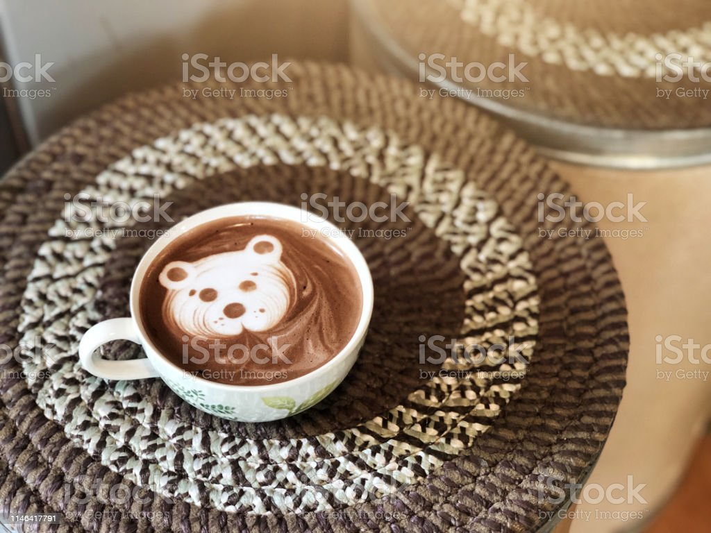 Cute bear face latte art Cocoa in white cup on paper box table ; cute...