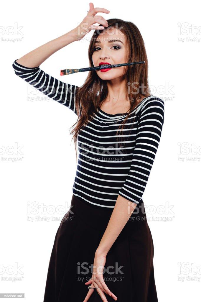 Cute beautiful girl artist Brush teeth bit into the paint stock photo