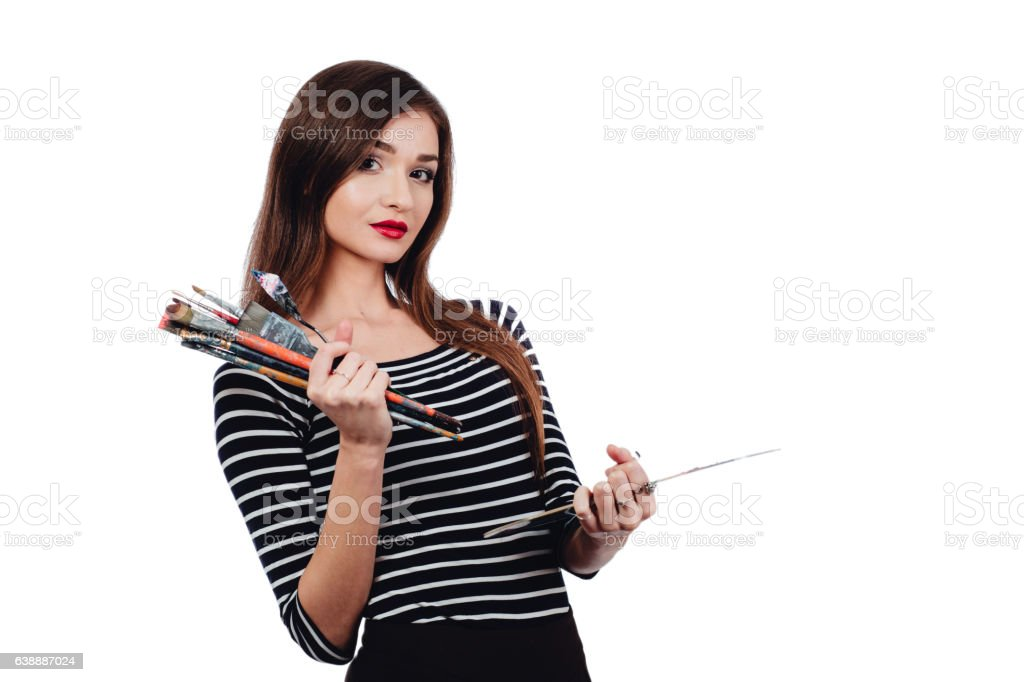Cute beautiful girl artist holding a palette and brush in stock photo