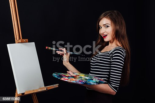655303558 istock photo Cute beautiful girl artist painting a picture on canvas an 638815360