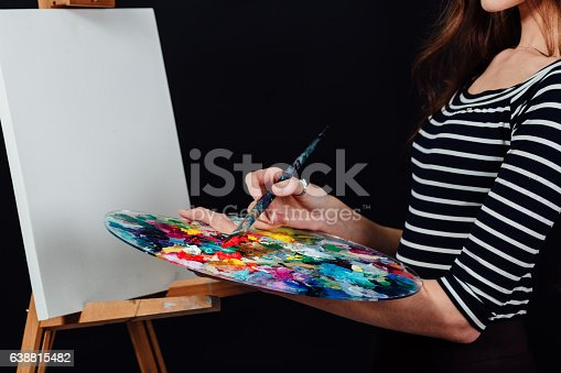 655303558 istock photo Cute beautiful girl artist painting a picture on canvas an 638815482
