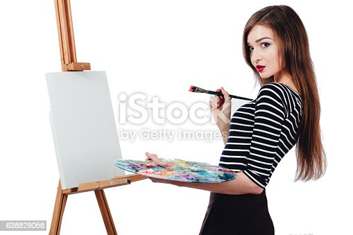 istock Cute beautiful girl artist painting a picture on  canvas  easel 638829058