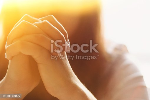 Cute beautiful girl folded her hands in prayer. A woman asks God for help.